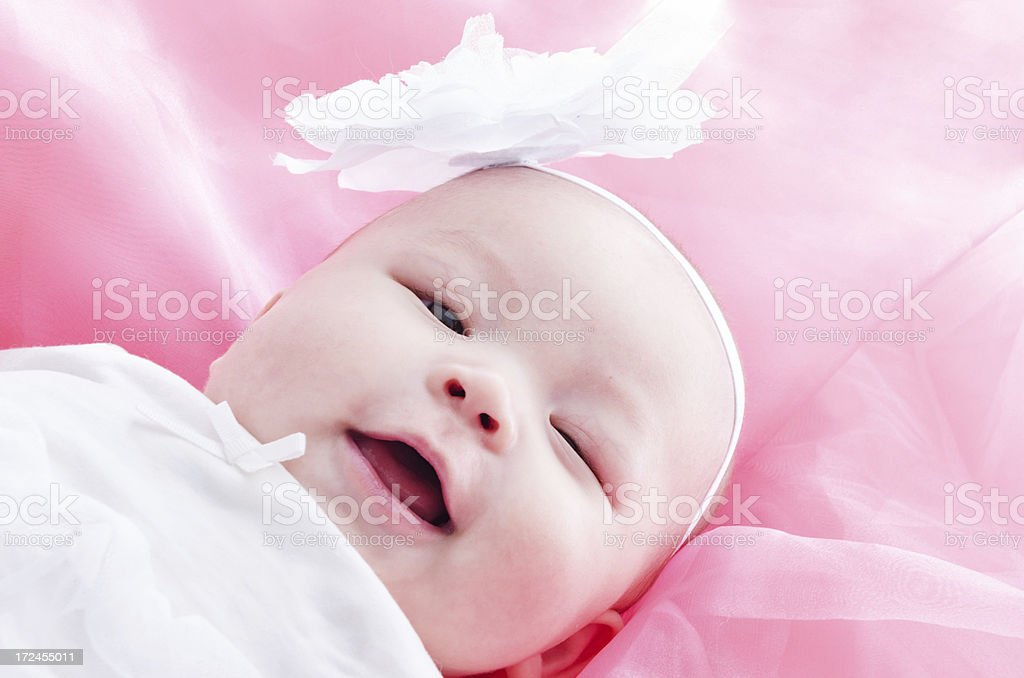 Laughing mixed race baby girl on pink. royalty-free stock photo