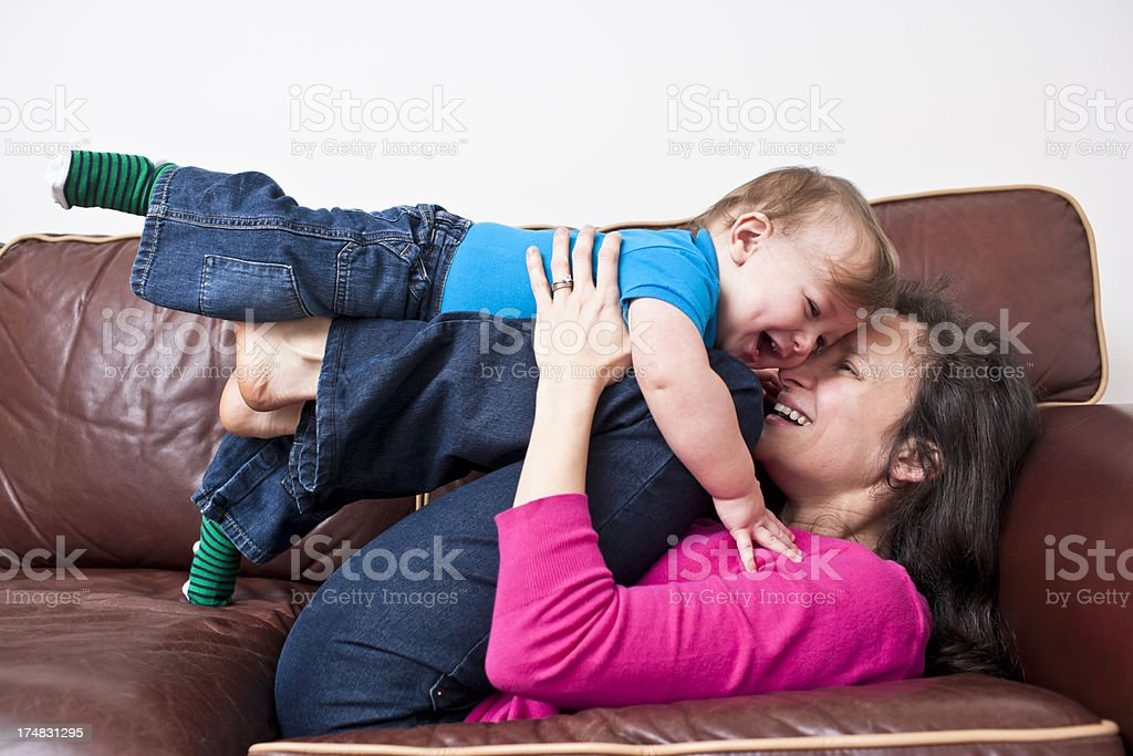 Laughing mother and child playtime on leather sofa royalty-free stock photo