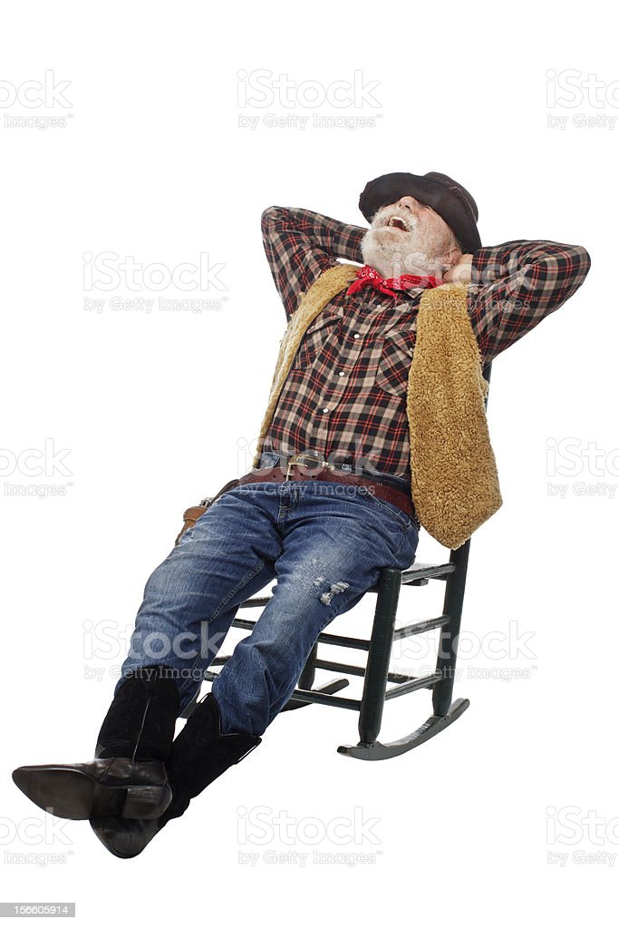 Laughing old cowboy leans back in rocking chair royalty-free stock photo