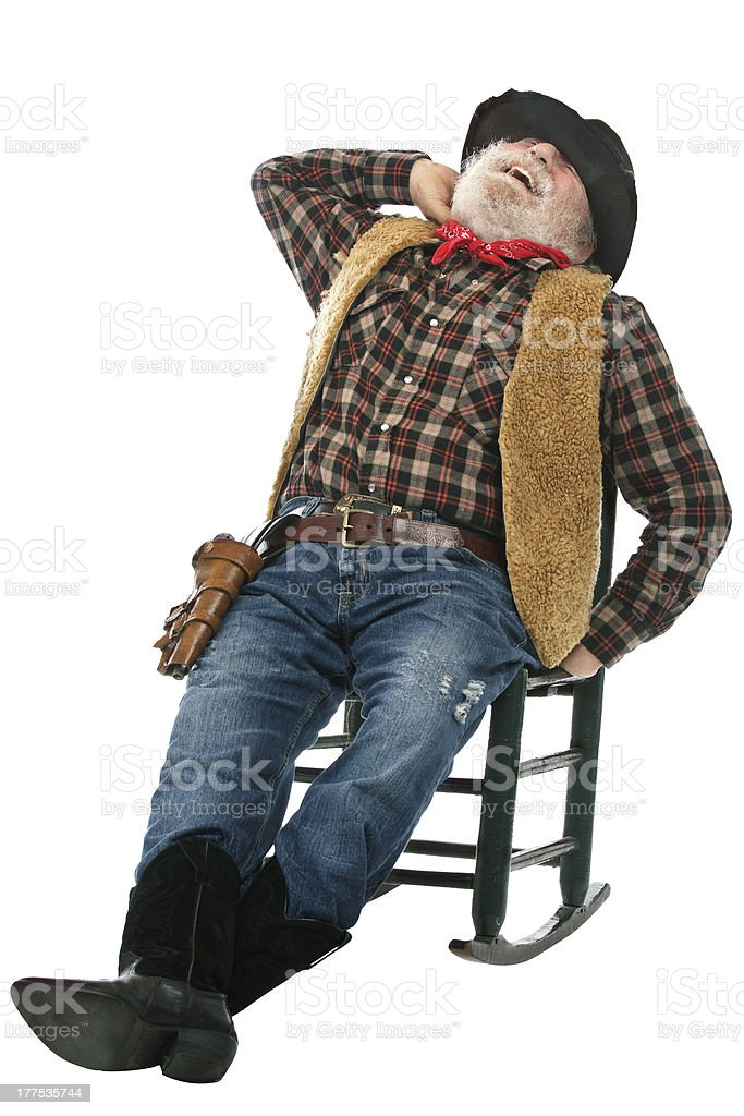 Laughing old cowboy leans back in rocking chair stock photo