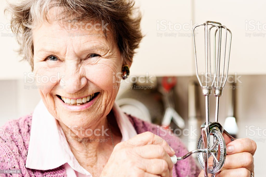 Laughing old woman holding old-fashioned egg beater stock photo