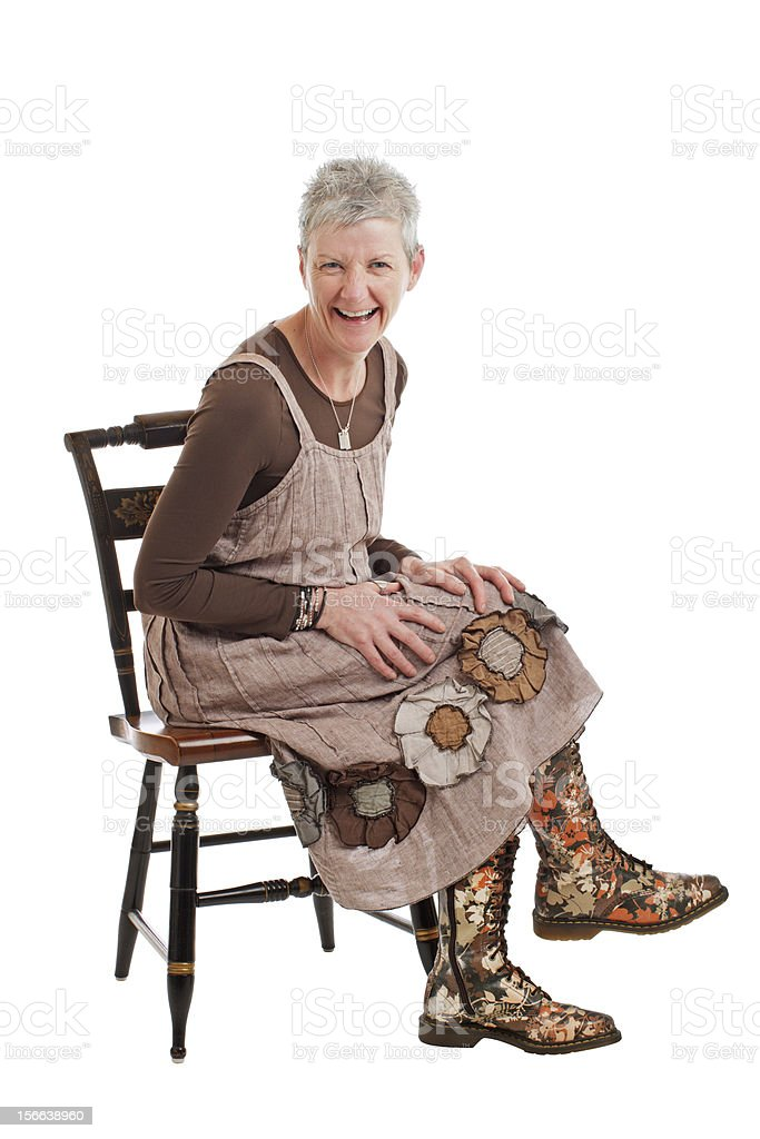 Laughing older woman in flowered boots sits sideways royalty-free stock photo