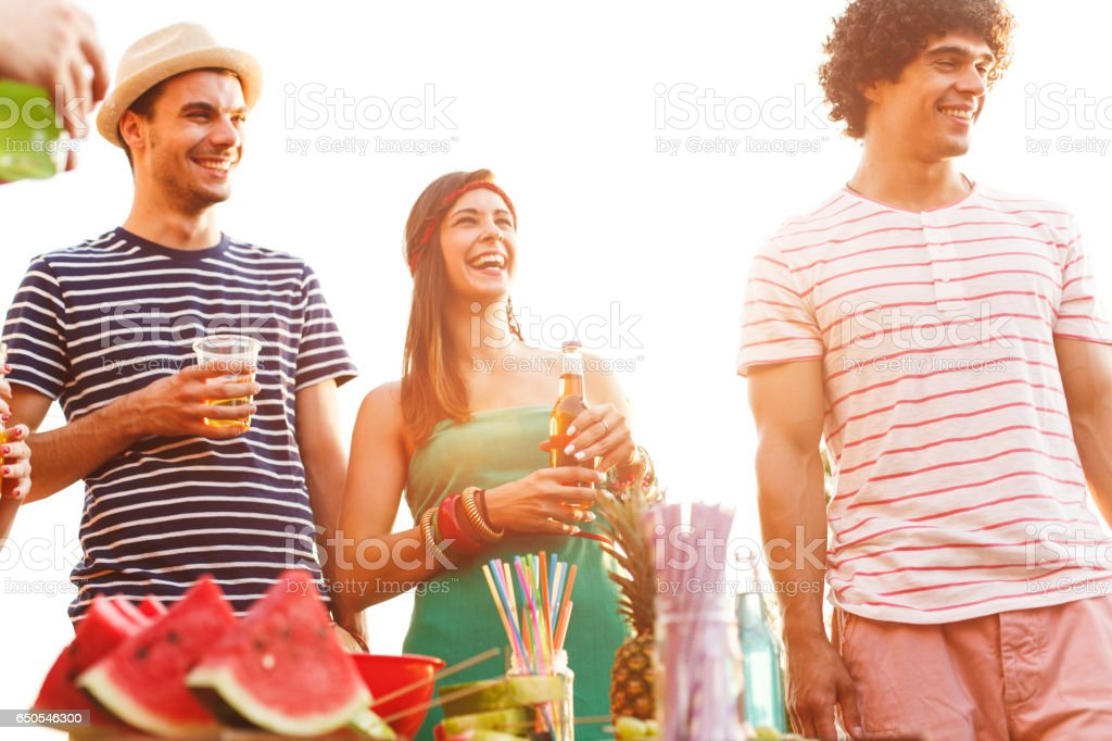 Laughing people having drinks on a party stock photo