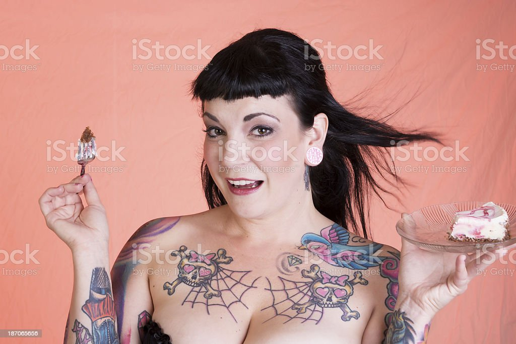 Horizontal studio shot on coral pink of happy tattooed mid adult...