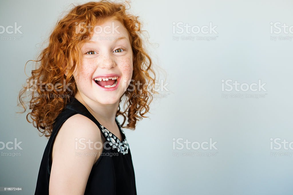 Laughing redhead little girl with freckles and missing tooth. stock photo