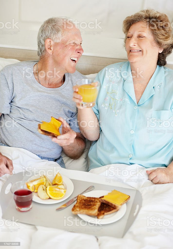 Laughing senior couple having fun together during breakfast royalty-free stock photo