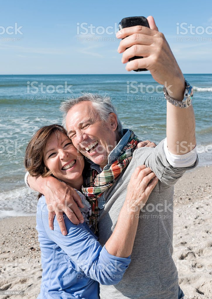 Laughing senior couple on beach making selfie with mobile stock photo