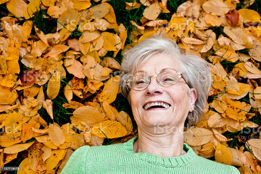laughing senior woman lays between leafs in autumn park royalty-free stock photo