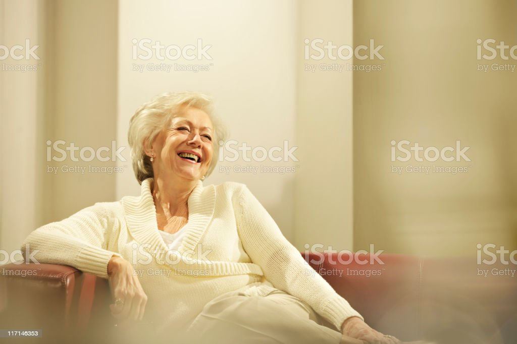 Laughing senior woman on red sofa royalty-free stock photo