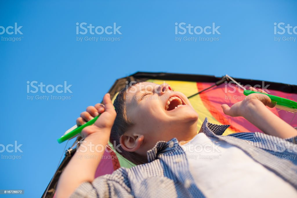 Laughing small boy holding a kite over his head against a blue sky stock photo