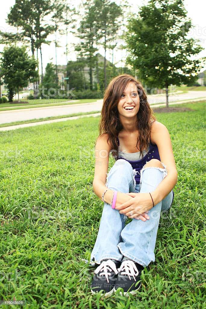 Laughing Teenage Girl Sitting in the Grass royalty-free stock photo