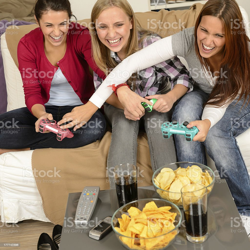 Laughing teenage girls playing with video game royalty-free stock photo