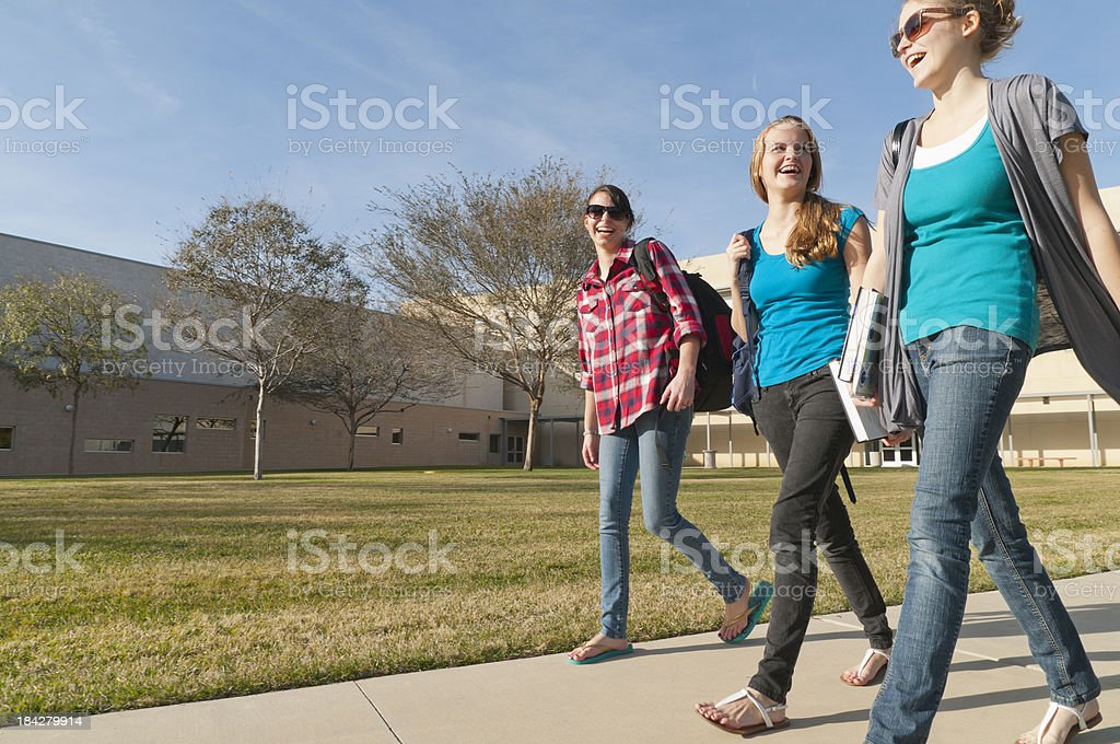 Laughing Teenage Girls Walking with School Building in Background royalty-free stock photo