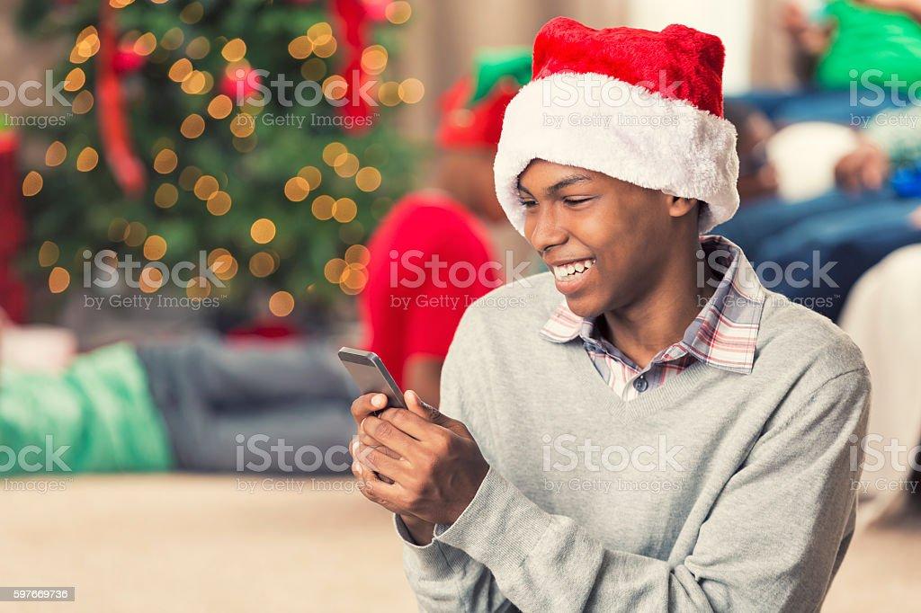 Laughing teenager playing on smart phone on Christmas morning stock photo