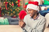 Laughing teenager playing on smart phone on Christmas morning
