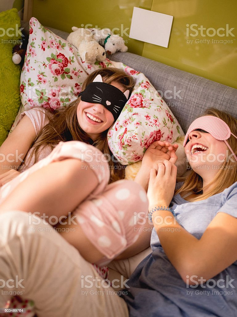 Laughing teens with sleeping masks on a bed in pyjamas stock photo
