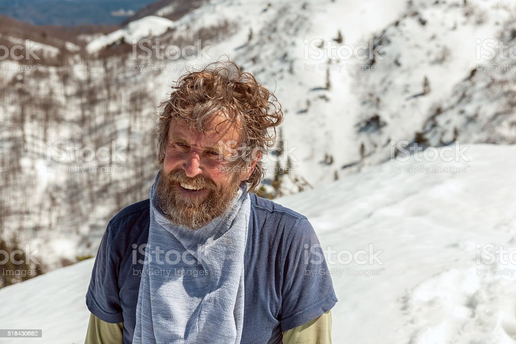 Laughing tired old man in wild mountains, Julian Alps,Slovenia stock photo