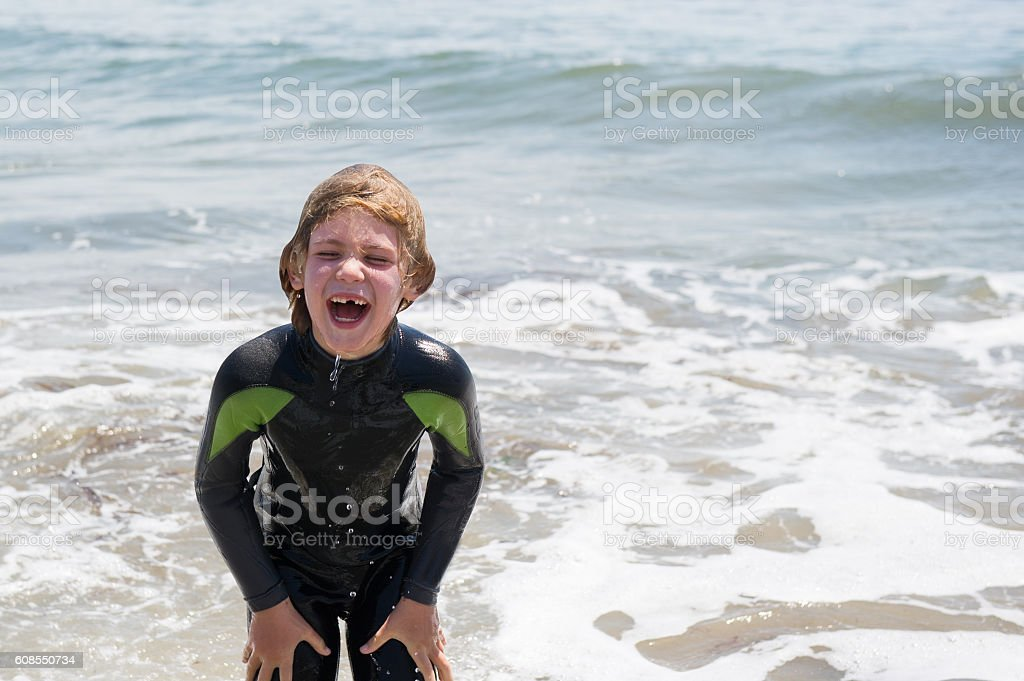 Laughing toothless child plays in ocean stock photo