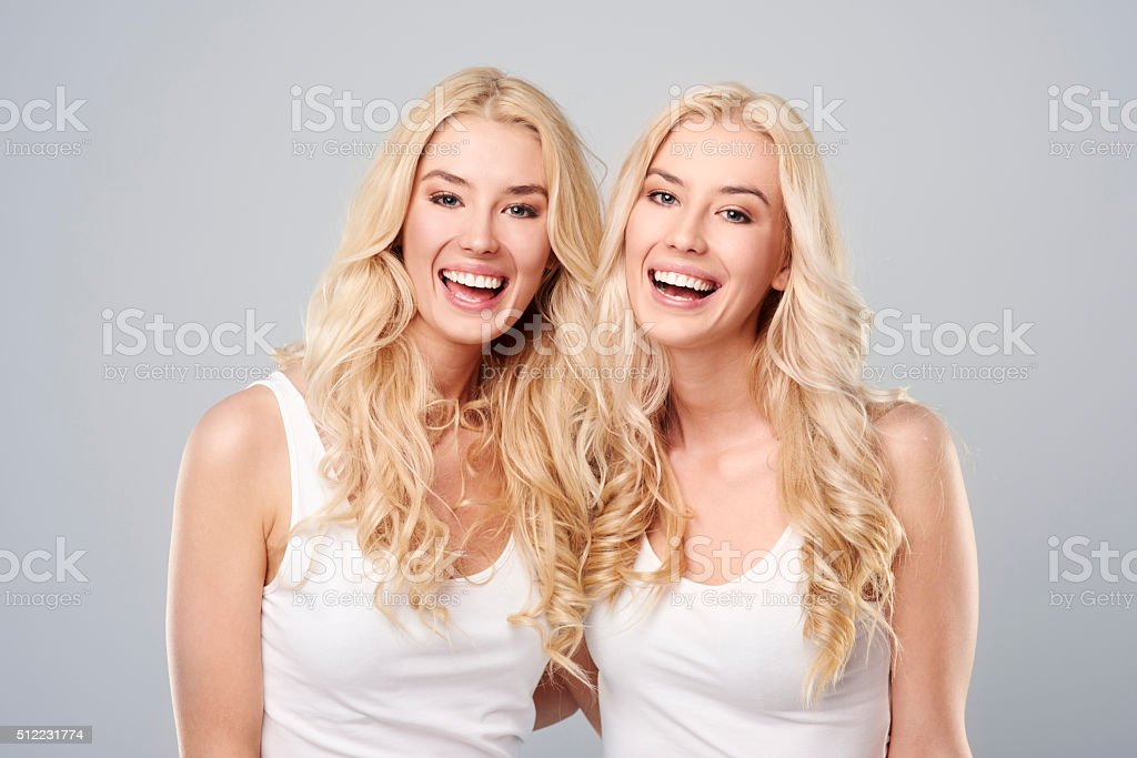 Laughing twins on the gray background stock photo