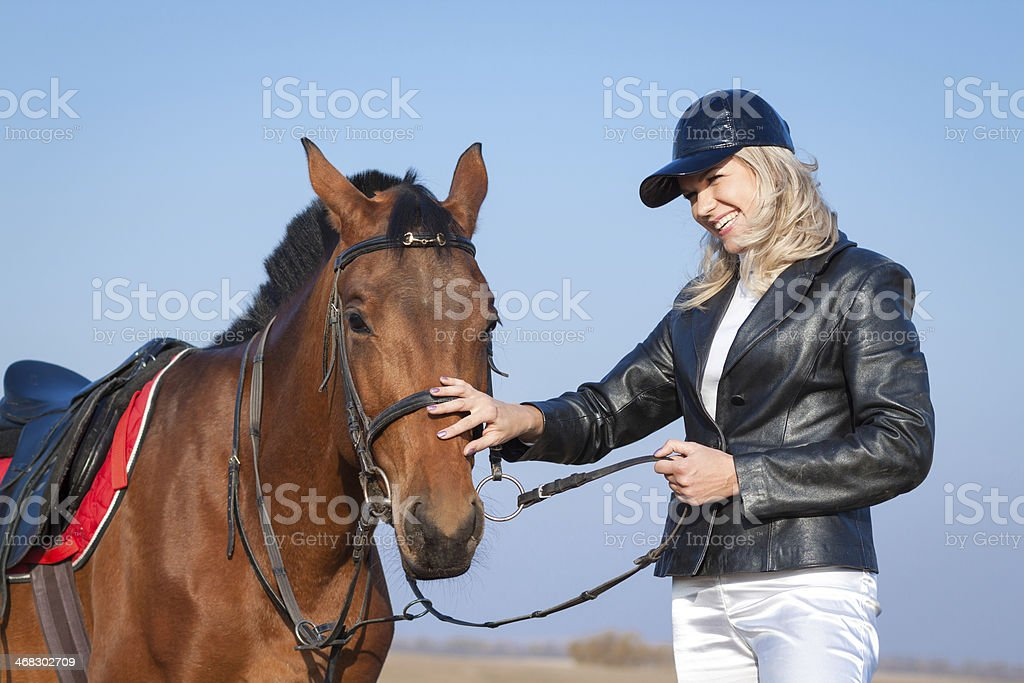 Laughing woman and horse on the sky background royalty-free stock photo