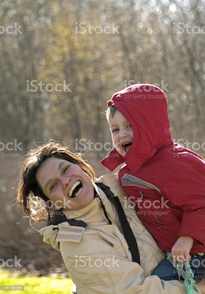 Laughing woman carrying  her son standing in front of trees royalty-free stock photo