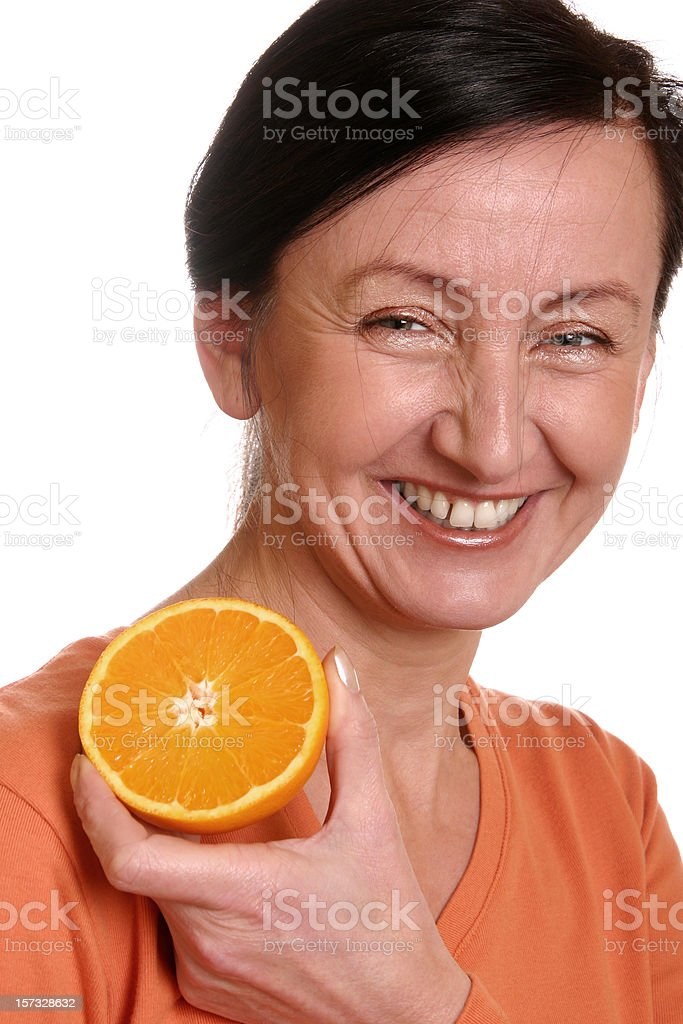 Laughing woman holding an orange stock photo