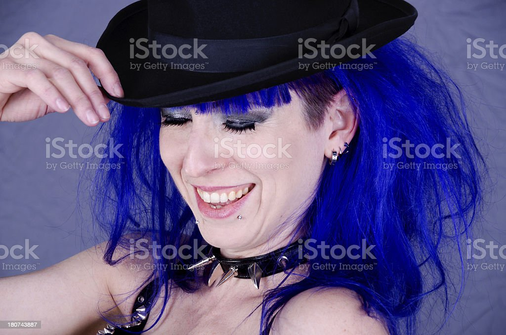 Laughing woman in blue hair touching hat. royalty-free stock photo