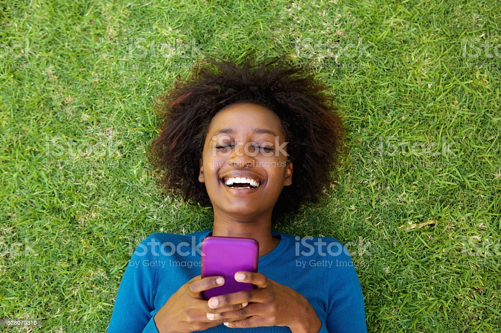 Laughing woman lying on grass with cell phone stock photo