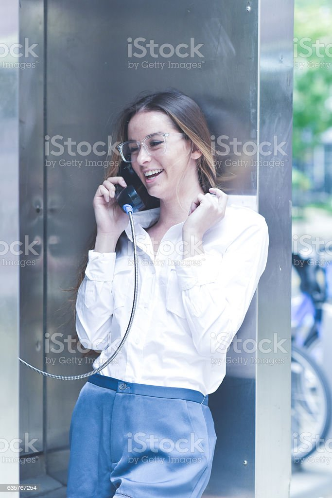 Laughing Woman Talking on Payphone stock photo
