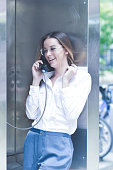 Laughing Woman Talking on Payphone