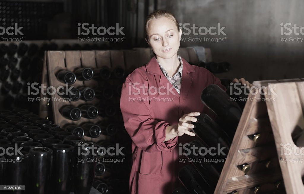 Laughing woman winery employee working in cellar stock photo