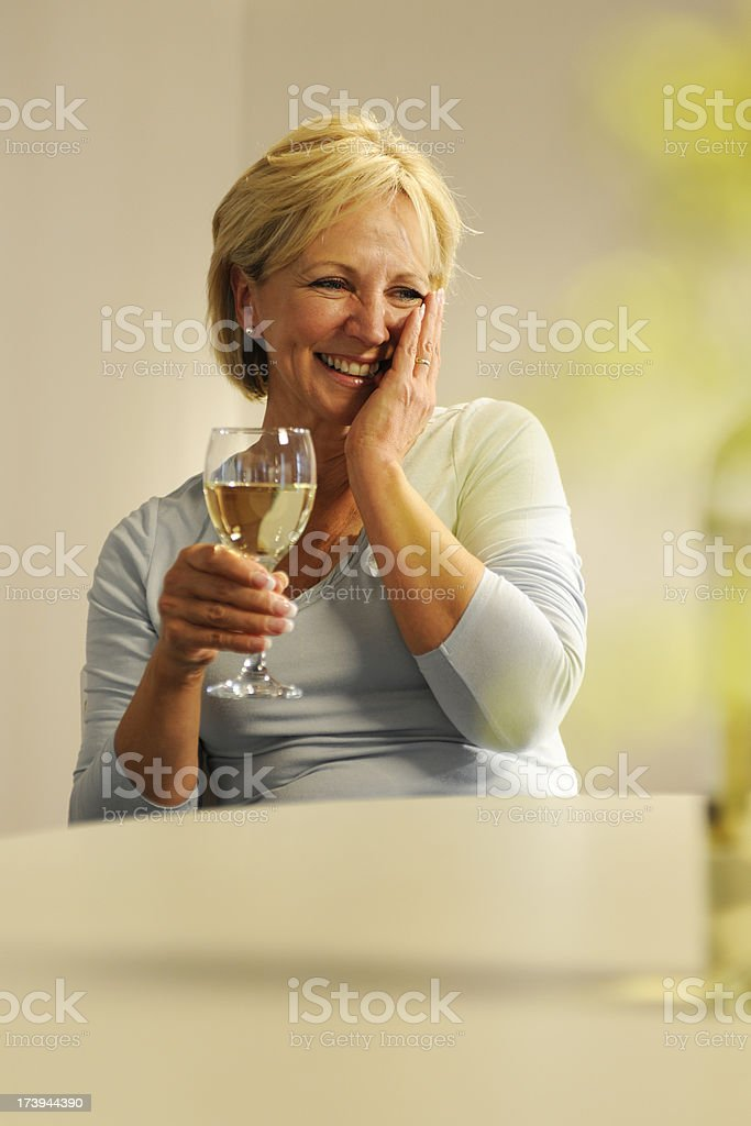 A laughing woman with hand on her cheek drinking white wine. royalty-free stock photo