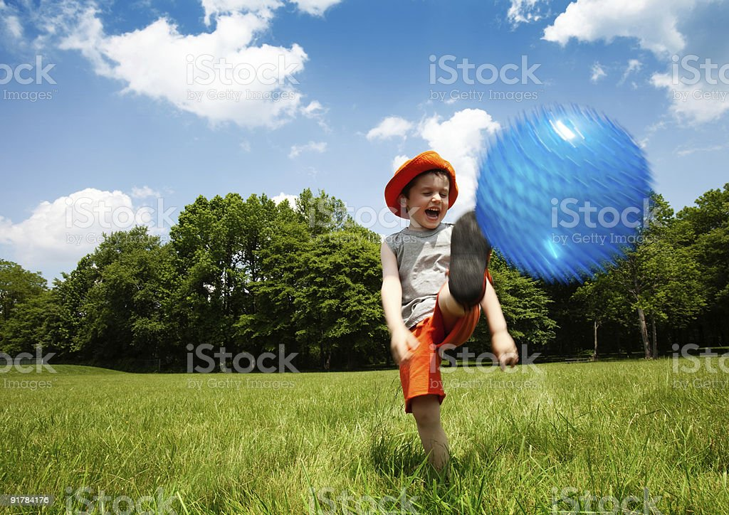 Laughing Young Boy Kicking a Ball in an Outdoor Park stock photo