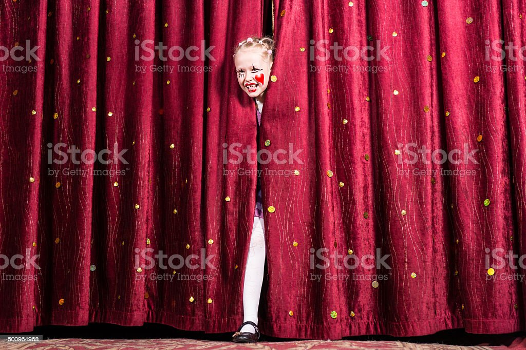 Laughing young girl making her entry on stage stock photo