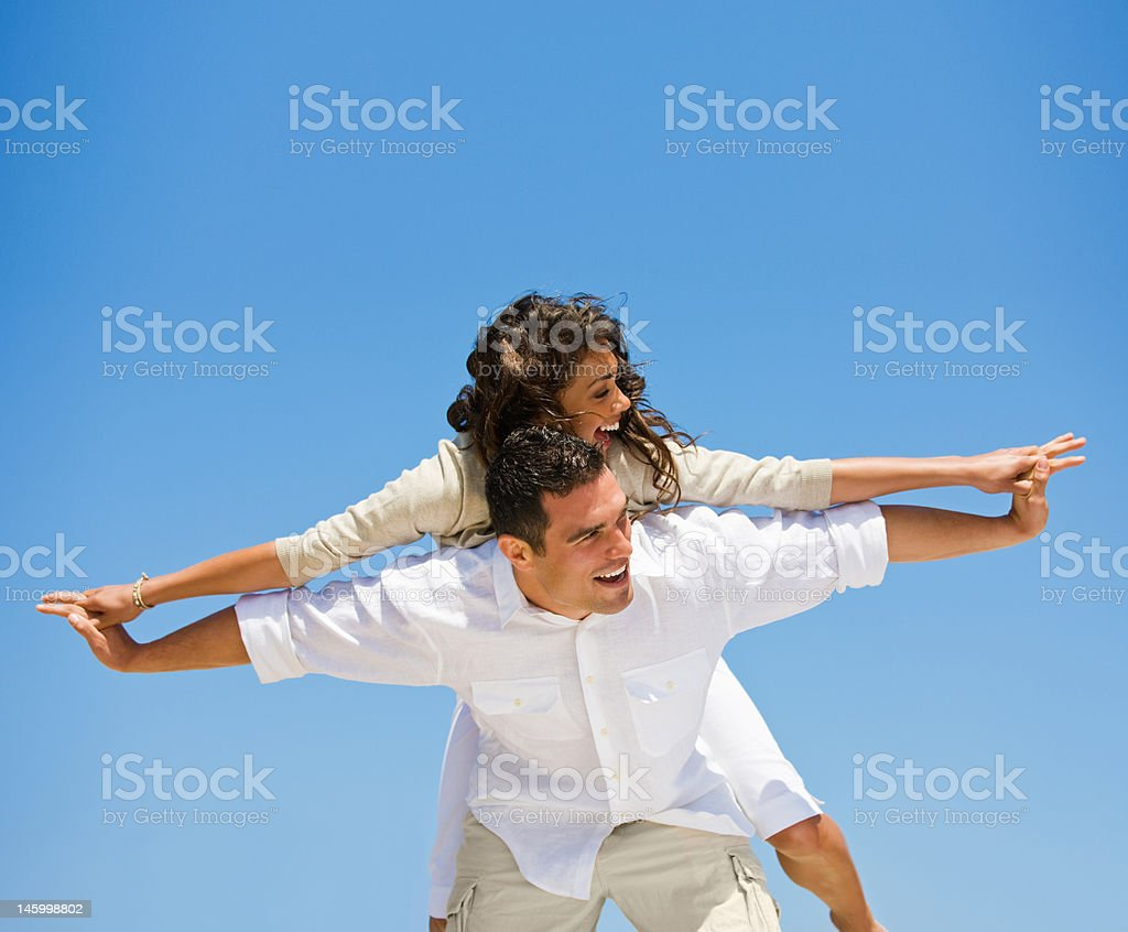 Laughing young man giving piggyback to woman against blue sky royalty-free stock photo