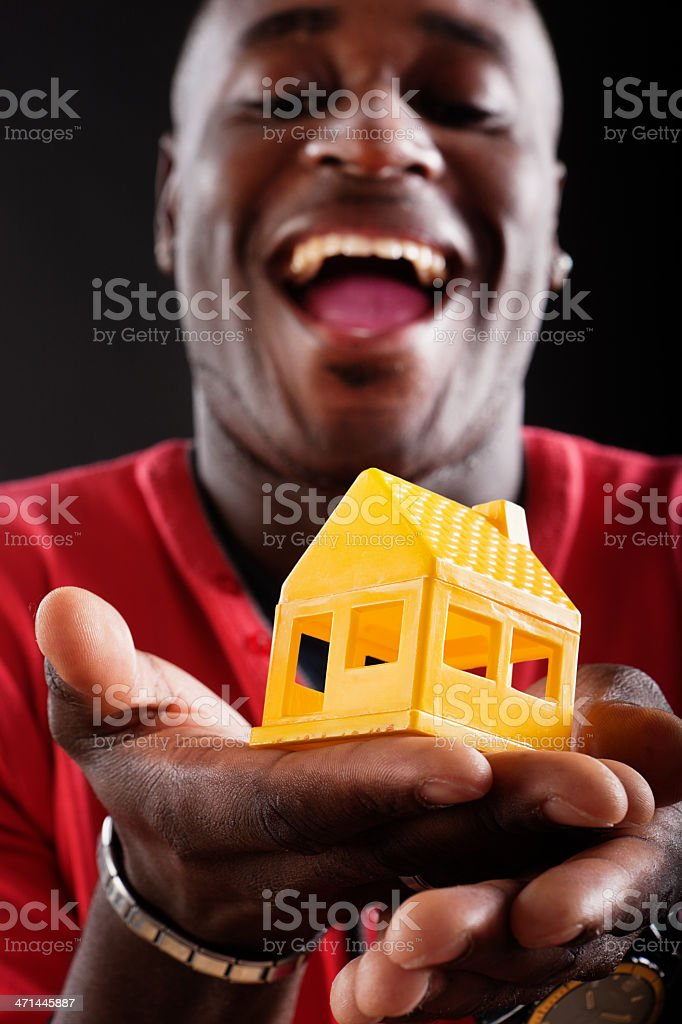 Laughing young man looks down at toy house he holds stock photo
