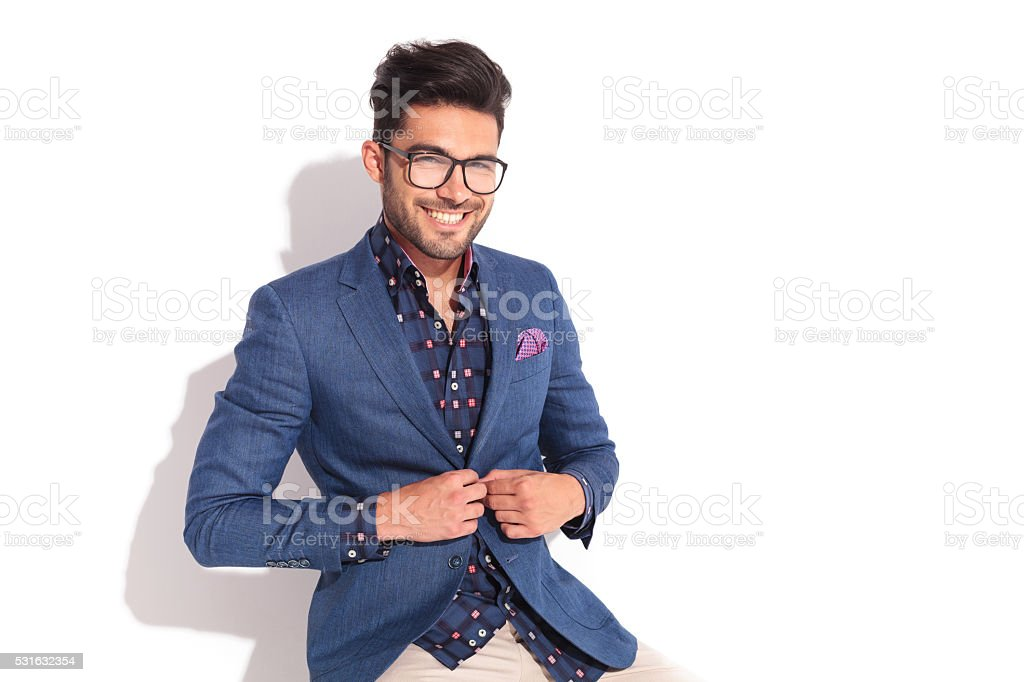 laughing young man unbuttoning his coat stock photo