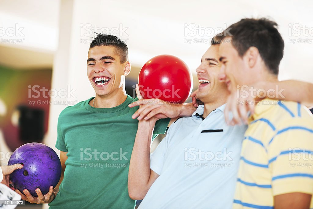 Laughing young men bowling together. stock photo