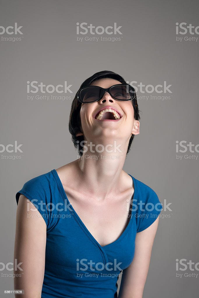 Laughing young short hair cutie wearing sunglasses stock photo