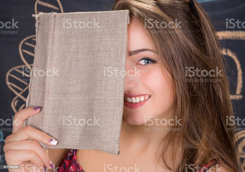 Laughing young student girl hides her face behind a book stock photo