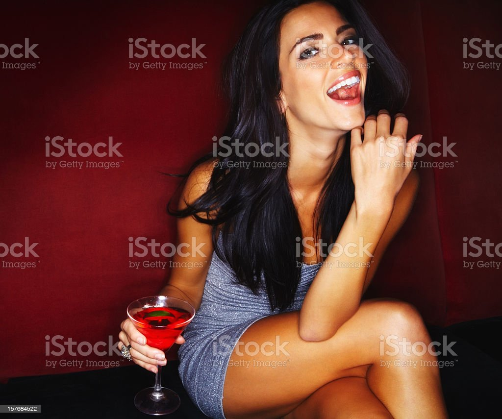 Laughing young woman holding a glass of martini stock photo