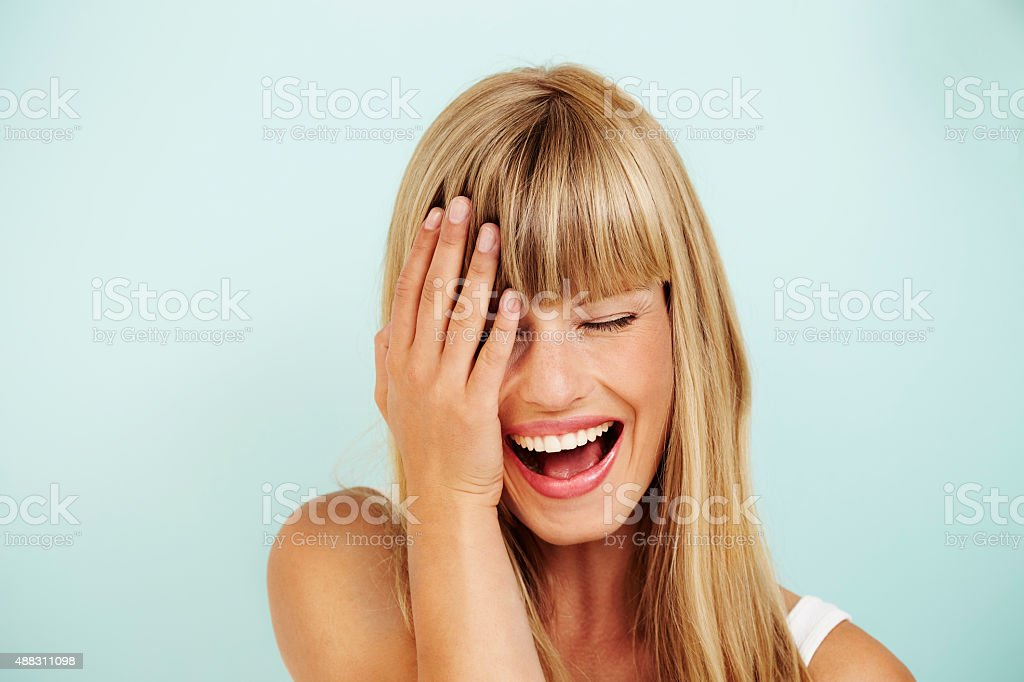 Laughing young woman in studio stock photo