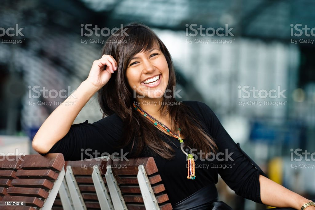 Laughing Young Woman Waiting on Train Station Bench royalty-free stock photo