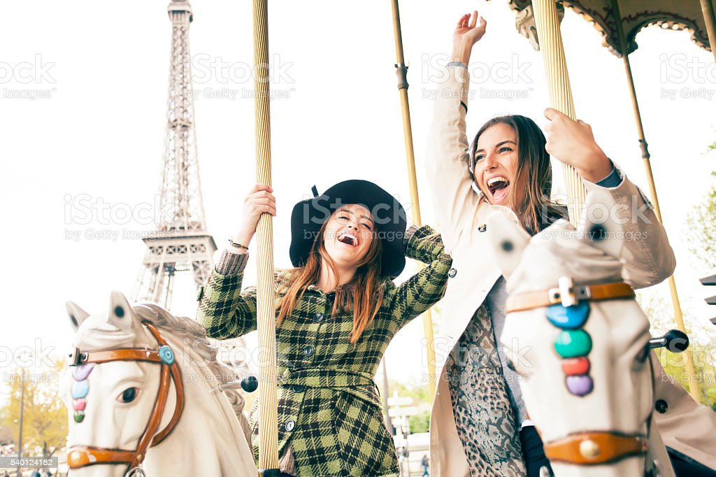 Laughing young women having fun on carousel at Eiffel Tower stock photo