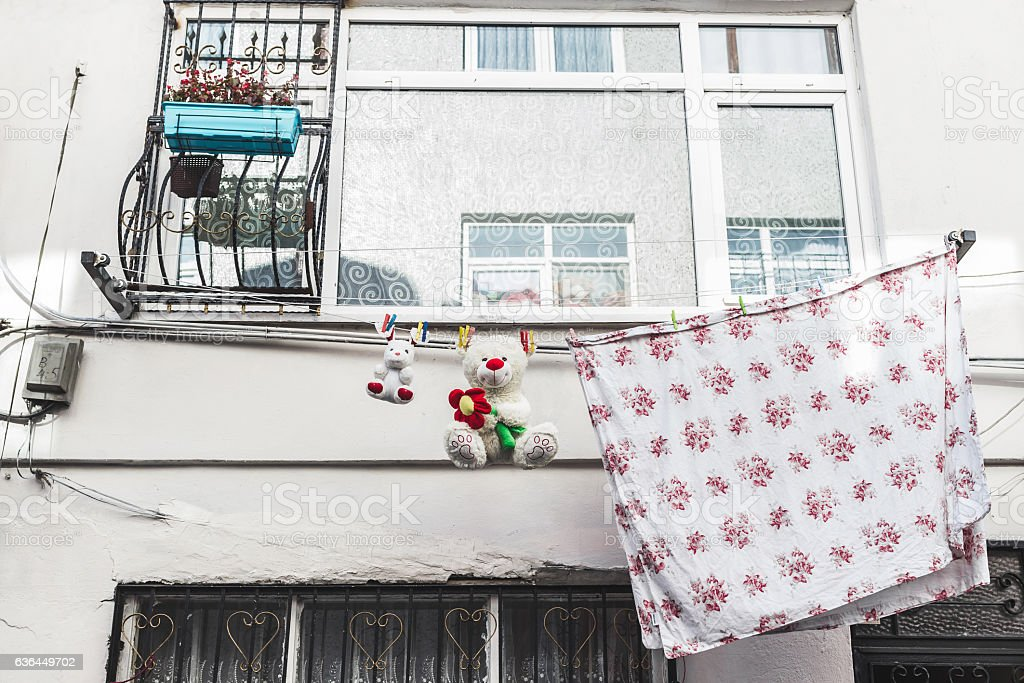 Laundry and funny teddy bear drying on the old street stock photo