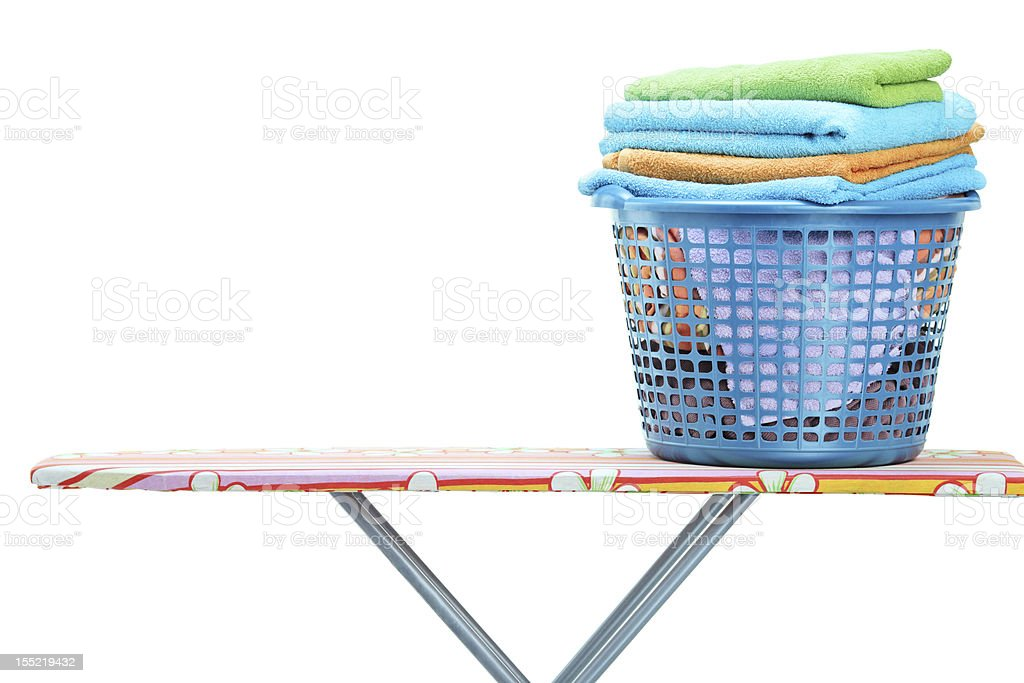 Laundry basket full of clothes on ironing board stock photo