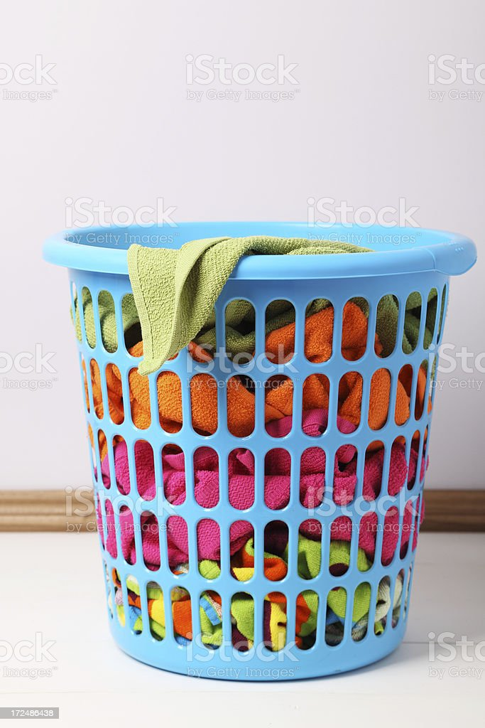 Laundry basket full of colorful towels royalty-free stock photo