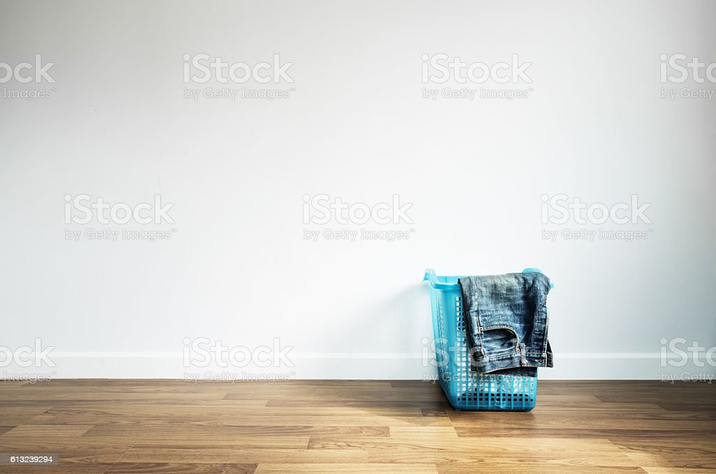 Laundry Basket on Wooden Floor and White Wall stock photo