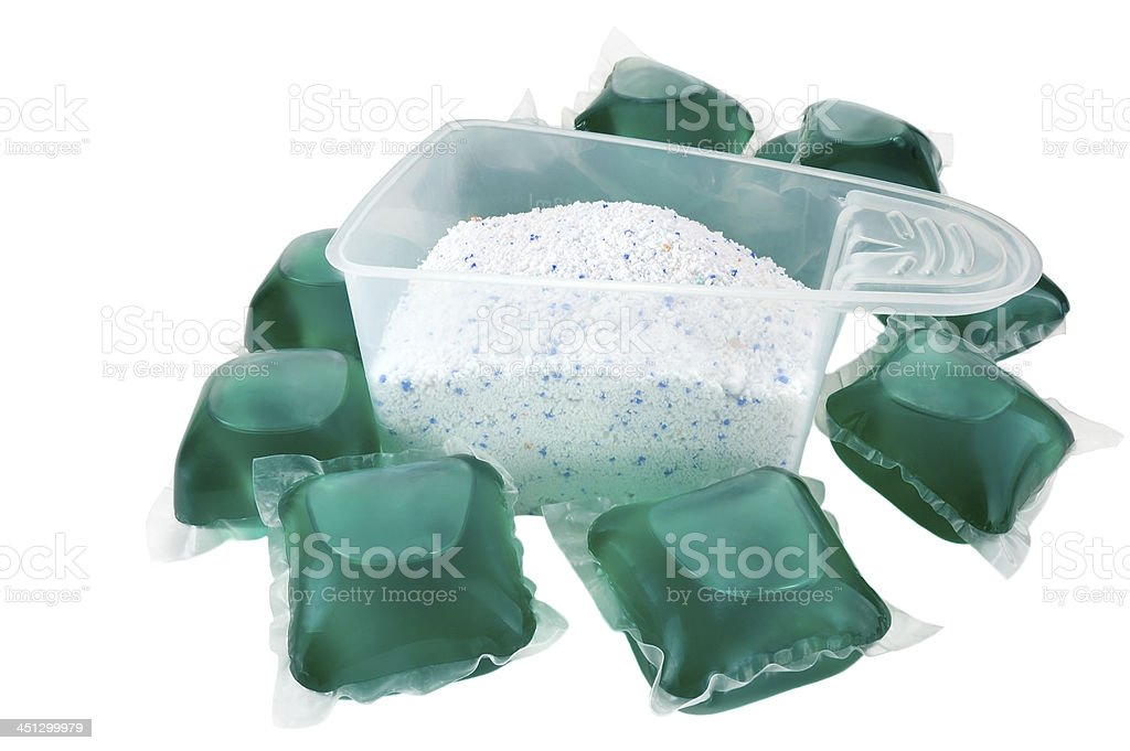 Laundry detergent capsules and a cup of washing powder stock photo