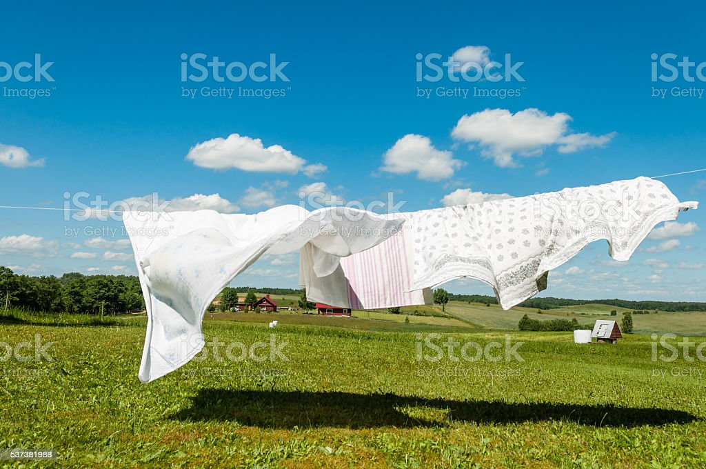 Laundry drying in a wind, white sheets on a wind stock photo